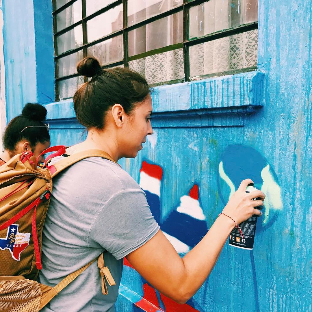 Amy spray painting a wall in Colombia