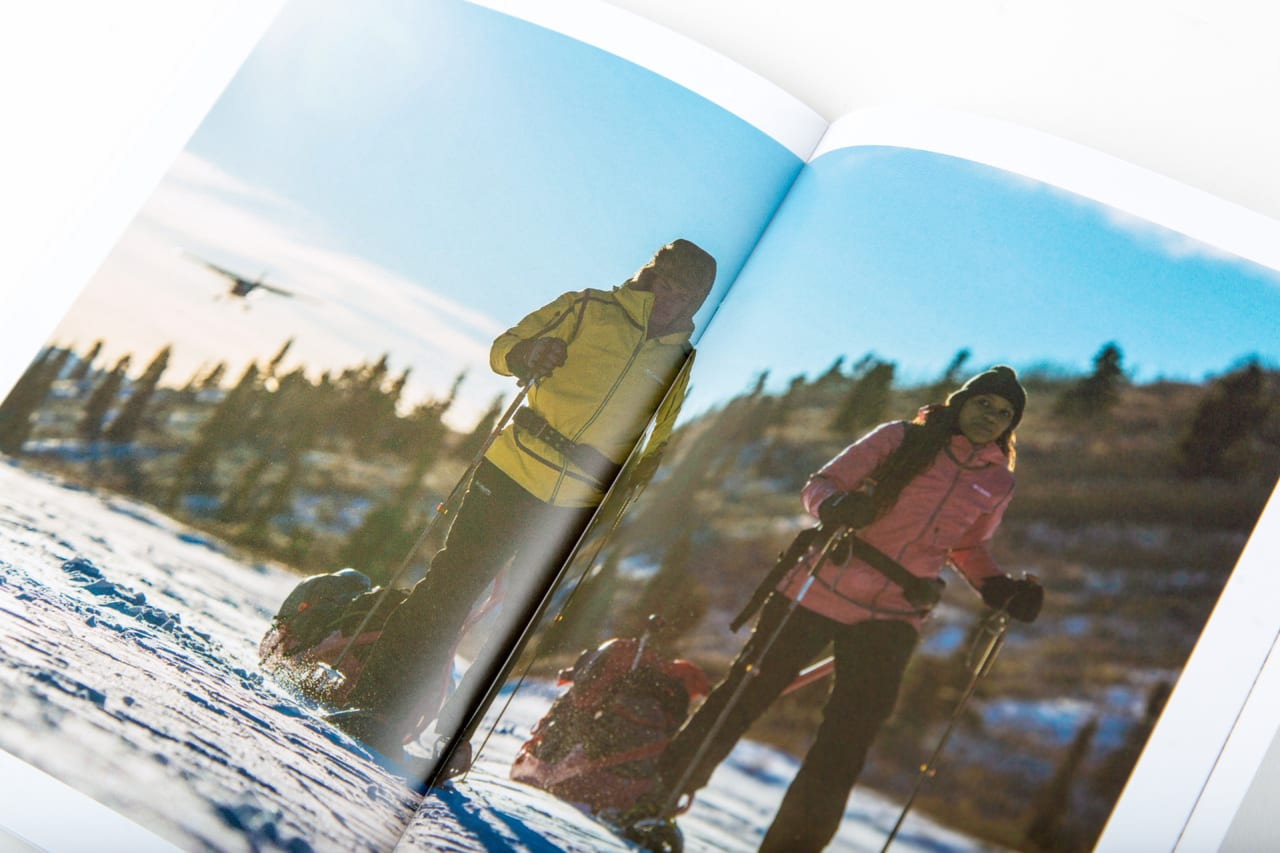 Newszine photo of two hikers snowshoeing in Yukon with plane in background.